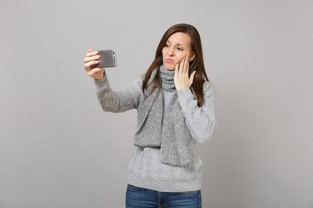 Traurige junge frau im pullover, schal, die hand auf die wange legt, selfie-aufnahme auf dem handy macht, videoanruf einzeln auf grauem hintergrund. gesunde mode lifestyle menschen emotionen konzept der kalten jahreszeit.