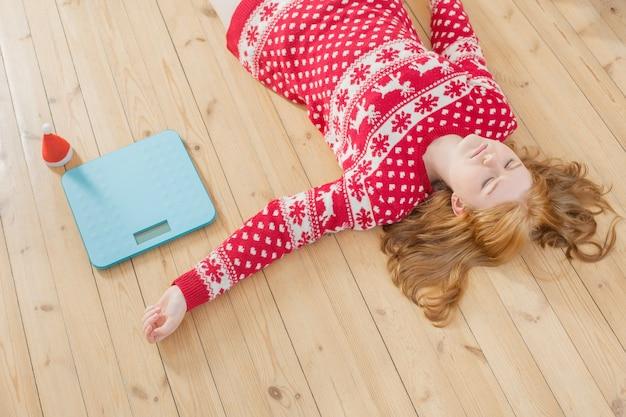 Traurige junge frau im weihnachtspullover mit blauer waage zur gewichtskontrolle zu hause