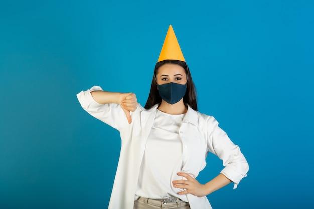 Traurige junge frau in der medizinischen maske im gelben geburtstagshut, der daumen unten auf blau zeigt