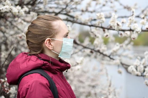 Traurige junge frau in der schützenden medizinischen gesichtsmaske. blühender baum an. frühlingsallergie.