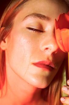 Traurige junge frau mit roter tulpe