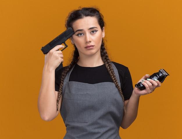 Traurige junge friseurin in uniform, die haarschneidemaschinen hält und pistole auf den tempel setzt, isoliert auf oranger wand
