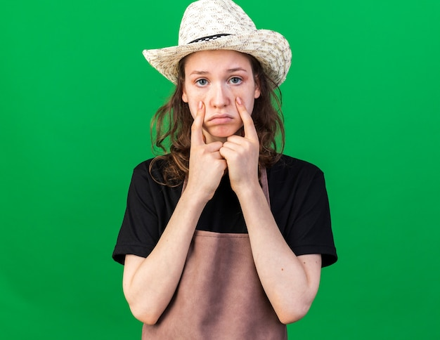 Traurige junge gärtnerin mit gartenhut, die die augenlider einzeln auf grüner wand herunterzieht