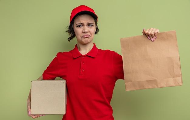 Traurige junge hübsche lieferfrau, die papierlebensmittelverpackungen und pappkarton hält