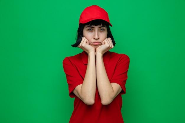 Traurige junge kaukasische lieferfrau, die sich die hände ans kinn legt und schaut