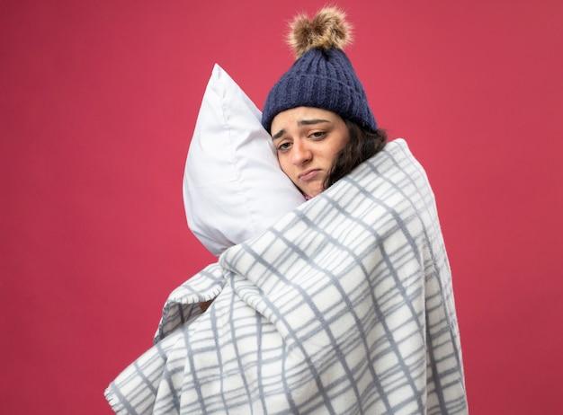Traurige junge kranke frau, die robe wintermütze und schal trägt, die in plaid gewickelt stehen, das in profilansicht umarmt kissen betrachtet seite betrachtet auf rosa wand