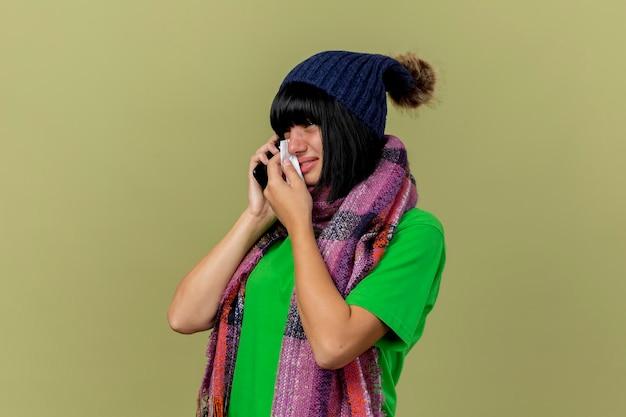 Traurige junge kranke frau, die wintermütze und schal trägt, die in der profilansicht stehen und am telefon sprechen und gerade abwischende tränen lokalisiert auf olivgrüner wand mit kopienraum suchen