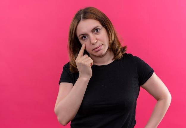 Traurige junge lässige frau, die schrei mit finger auf wange auf isoliertem rosa raum mit kopienraum gestikuliert
