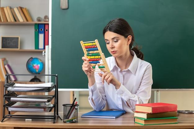 Traurige junge lehrerin, die am tisch mit schulwerkzeugen sitzt und abakus im klassenzimmer hält und betrachtet
