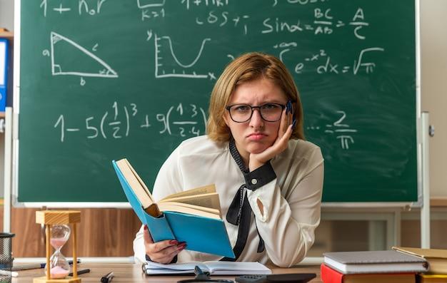 Traurige junge lehrerin mit brille sitzt am tisch mit schulwerkzeugen, die ein buch halten und die hand unter das kinn im klassenzimmer legen