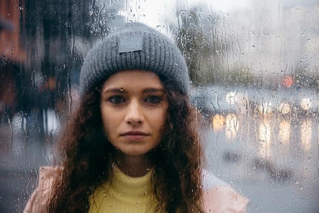 Traurige junge lockige frau bleiben allein am glas mit tropfen am regnerischen tag