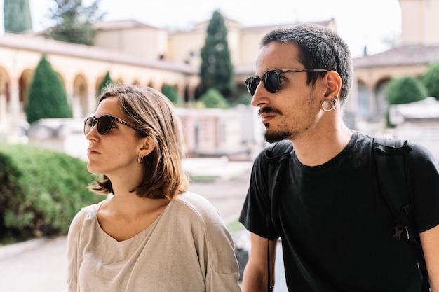 Traurige junge paare mit der sonnenbrille, welche die front am bologna-kirchhof, italien gegenüberstellt