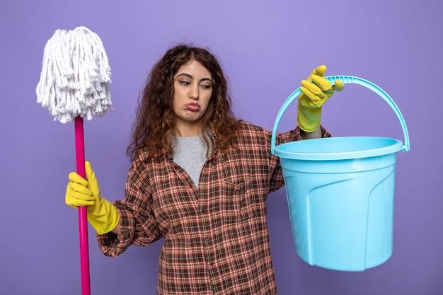 Traurige junge putzfrau mit handschuhen, die einen mopp mit blick auf den eimer in der hand hält
