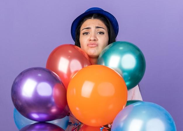 Traurige junge schöne frau mit partyhut, die hinter luftballons steht, isoliert auf blauer wand