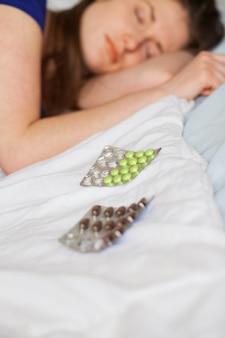 Traurige kaukasische frau, die mit pillen schläft