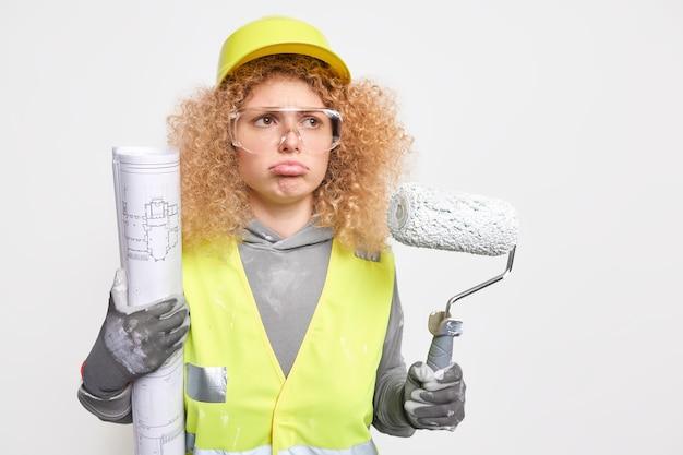 Traurige, lockige architektin trägt schutzhelm-arbeitsuniform, die professionelle hausbauarbeiterin ist, hält walze und blaupause erkennt einige fehler im projekt. industriegebäude