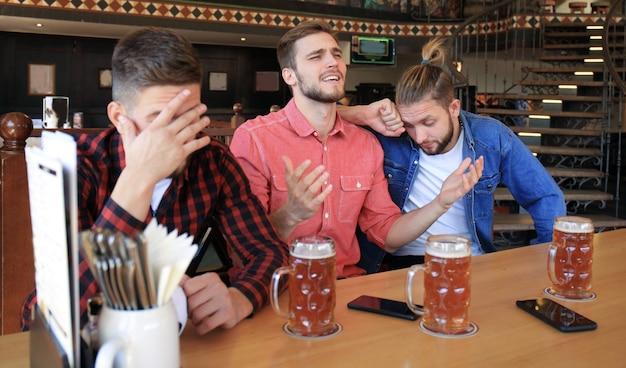Traurige männliche fußballfans, die das spiel an der bar beobachten und bier trinken.