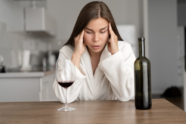 Traurige müde frau, die wein zu hause trinkt