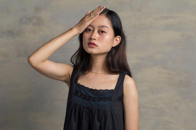 Traurige müde junge asiatische frau, die stirn berührt, die kopfschmerzen migräne oder depression hat
