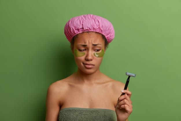 Traurige niedergeschlagene frau schaut auf rasiermesser, trägt kollagenpflaster auf, hat augenhautverjüngungsbehandlung, trägt nach dem duschen eine badekappe, will sich nicht die beine rasieren, isoliert auf grüner wand