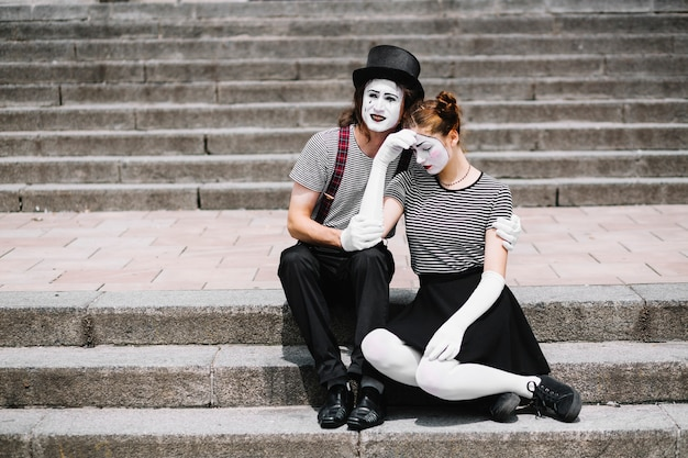 Traurige pantomimepaare, die auf treppenhaus sitzen