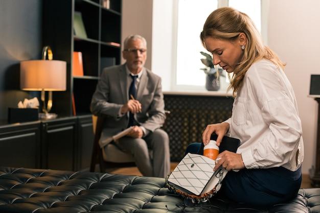 Traurige patientin, die pillen aus ihrer handtasche nimmt, während sie auf der couch in ihrem büro als psychoanalytiker sitzt