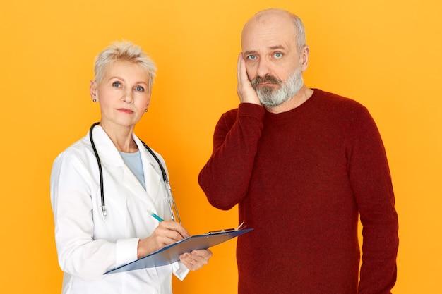Traurige pensionierte weibliche praktizierende im weißen medizinischen mantel, der zwischenablage hält, erzählt ihrem älteren patienten über diagnose und behandlung