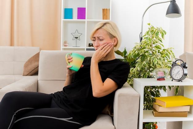 Traurige schöne blonde russische frau, die auf sessel liegt, der hand auf gesicht hält tasse im wohnzimmer hält
