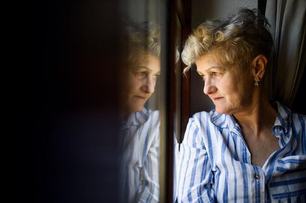 Traurige seniorin, die zu hause am fenster steht, corona-virus und quarantänekonzept. platz kopieren.