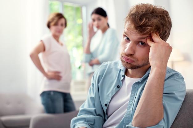 Traurige stimmung. porträt eines müden jungen mannes, der sie ansieht, während er seine stirn berührt