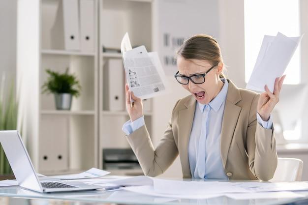 Traurige stressige junge geschäftsdame in gläsern, die am tisch sitzen und schreien, während sie papiere überprüfen und fehler herausfinden