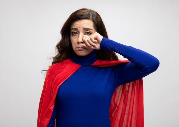 Traurige superfrau mit rotem umhang setzt faust auf augenlid isoliert auf weißer wand
