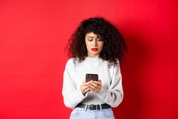 Traurige und besorgte frau, die nachricht auf smartphone liest, schlechte nachrichten in den sozialen medien erhält und gegen rote wand steht.