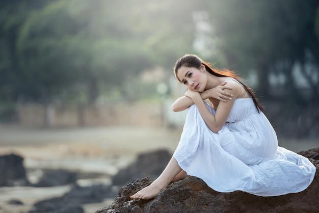 Traurige und deprimierte frau tief im gedanken allein draußen.