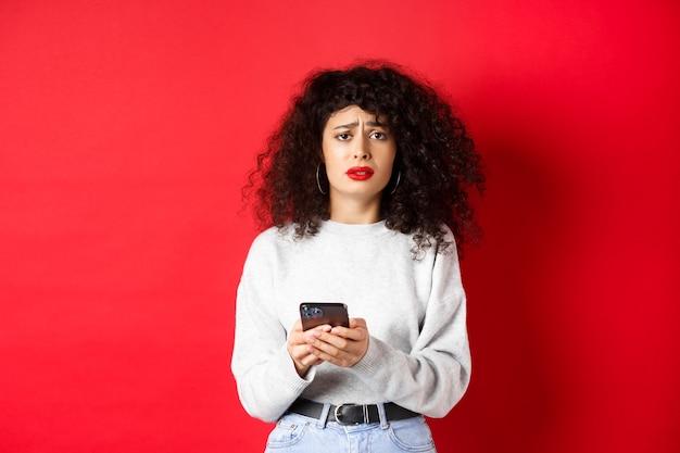 Traurige und düstere frau mit lockigem haar, die die stirn runzelt und sich nach dem lesen der smartphone-nachricht verärgert fühlt und enttäuscht vor rotem hintergrund steht