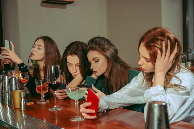 Traurige und müde freundinnen, die an der bar etwas trinken. sie sitzen an einem holztisch mit cocktails. sie tragen freizeitkleidung.