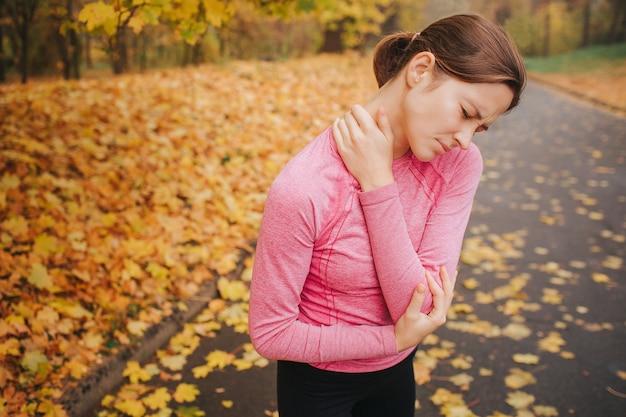 Traurige und verärgerte junge frau leiden unter schmerzen im nacken- und ellbogenbereich. sie hält die augen geschlossen. frau ist allein im park.