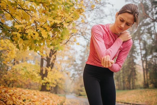 Traurige und verärgerte junge joggerin steht im herbstpark und hält hände am hals. sie fühlt dort schmerzen. junge frau leiden.