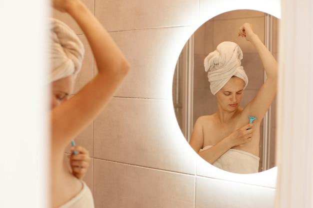 Traurige unglückliche junge erwachsene frau, die achselhöhle im badezimmer rasiert, ihren körper betrachtet, enthaarungsprozess, attraktive frau mit nackten schultern und in weißes handtuch gewickelt.