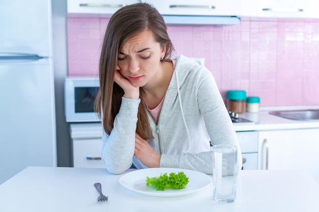 Traurige unglückliche junge frau ist vom nähren müde und möchte nicht organisches, sauberes gesundes lebensmittel essen