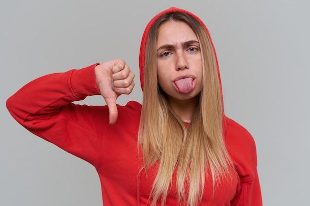 Traurige verärgerte blonde junge frau im roten kapuzenpulli, der zunge zeigt und daumen unten über graue wand zeigt