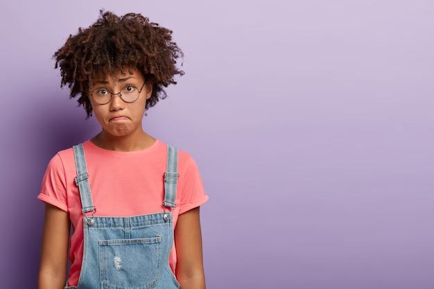 Traurige verwirrte junge frau mit einem afro, der in overalls posiert