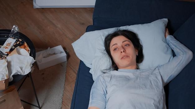 Traurige verzweifelte depressive junge frau, die allein sitzt und weinend auf dem sofa in einem schmutzigen zimmer liegt und an ...