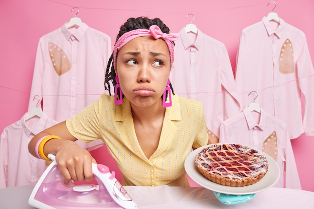 Traurige, verzweifelte, dunkelhäutige frau mit dreadlocks hält gebackenen kuchen auf dem teller und verwendet ein elektrisches bügeleisen, um kleidung zu streicheln, fühlt sich müde, trägt ein stirnband auf dem kopf