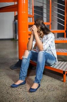 Traurige weibliche exekutive, die auf treppe sitzt