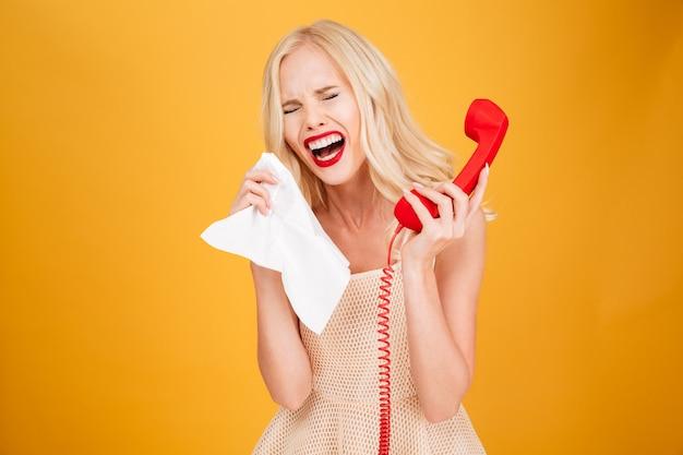 Traurige weinende junge blonde frau, die per telefon spricht.