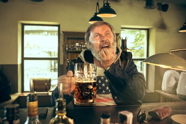 Trauriger älterer mann, der alkohol in der kneipe trinkt und ein sportprogramm im fernsehen sieht