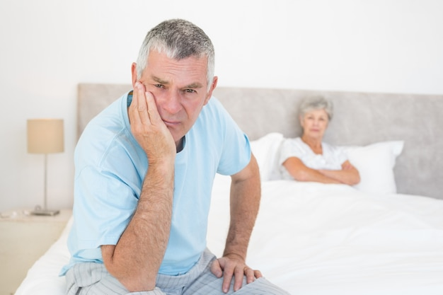 Trauriger älterer mann mit frau im bett