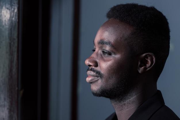 Trauriger afrikanischer mann im dunklen raum, zurückhaltender stil