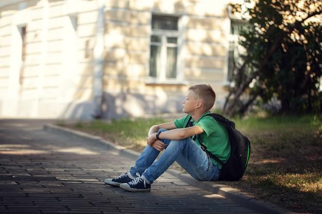 Trauriger alleinjunge, der draußen auf straße im park sitzt.